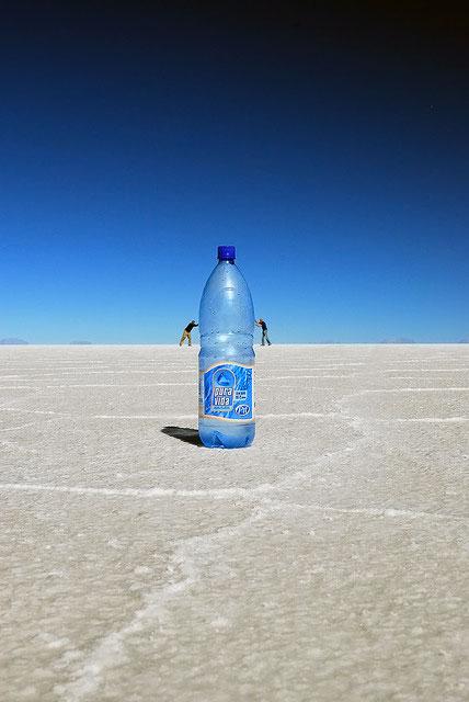 Büyük bir su şişesini itelemeye çalışan küçük insanlar