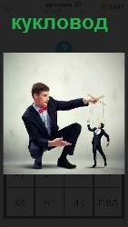 парень кукловод манипулирует людьми на веревочках