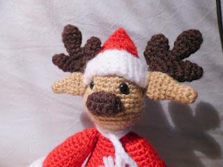 Crochet amigurumi reindeer dressed in santa suit
