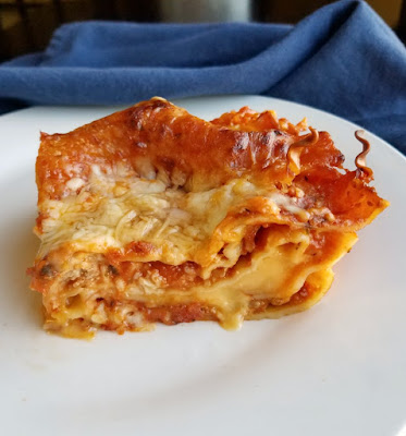 piece of american cheese lasagna with melty velveeta cheese layer in the middle