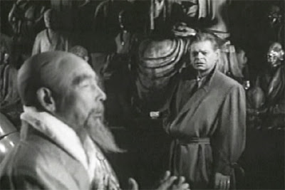 Larry (Peter Dyneley) confronts a temple priest (Shinpei Takagi)