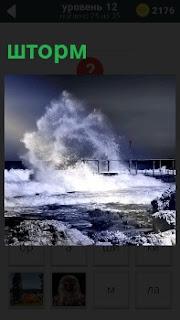 Выше причала поднимаются волны и вода накатывает на берег во время шторма, синее небо