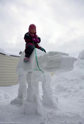 Lustiges Spassbild Kind - Mädchen reitet auf Schneeskulptur Star Wars