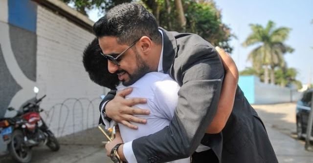 Yaqoob Yusuf Ahmed Mubarak abrazando al niño que estudiaba bajo un poste de luz