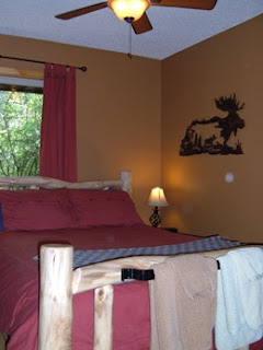 Charming log bed with a red duvet comforter, brown walls, metal art work of a moose on the wall, bed lamp, and a ceiling fan.  Brown and green towel sets hanging on a rod iron towel bar at the foot of the bed.
