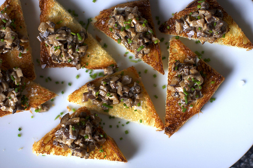 a creamed mushroom and chive spread on buttered toast is a delicious party appetizer