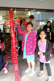 Youngsters Hina and Farah add the last few red plastic cups to their tower.