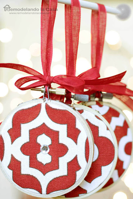 red and white fabric on embroidery hoops with red ribbon ornaments with a lighted background
