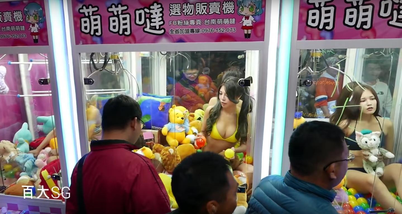 Garotas de biquíni em máquinas de Gatcha Ufo pra atrair clientes