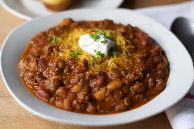 A bowl of the Perfect Chili Recipe topped with cheese, sour cream, and parsley.
