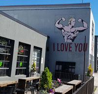"Body builder painted on the side of a building, with ""I love you"" below"