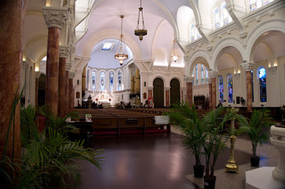 Interior shot facing the apse from behind the pews showing the columns, pews and vaulted ceiling