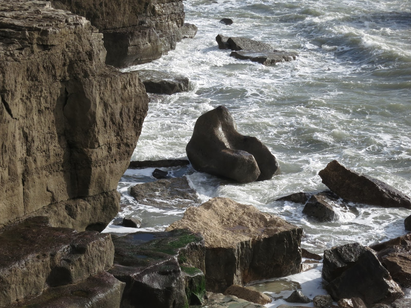 Sea washes over rocks at base of cliff - Portland Bill, Dorset, England.