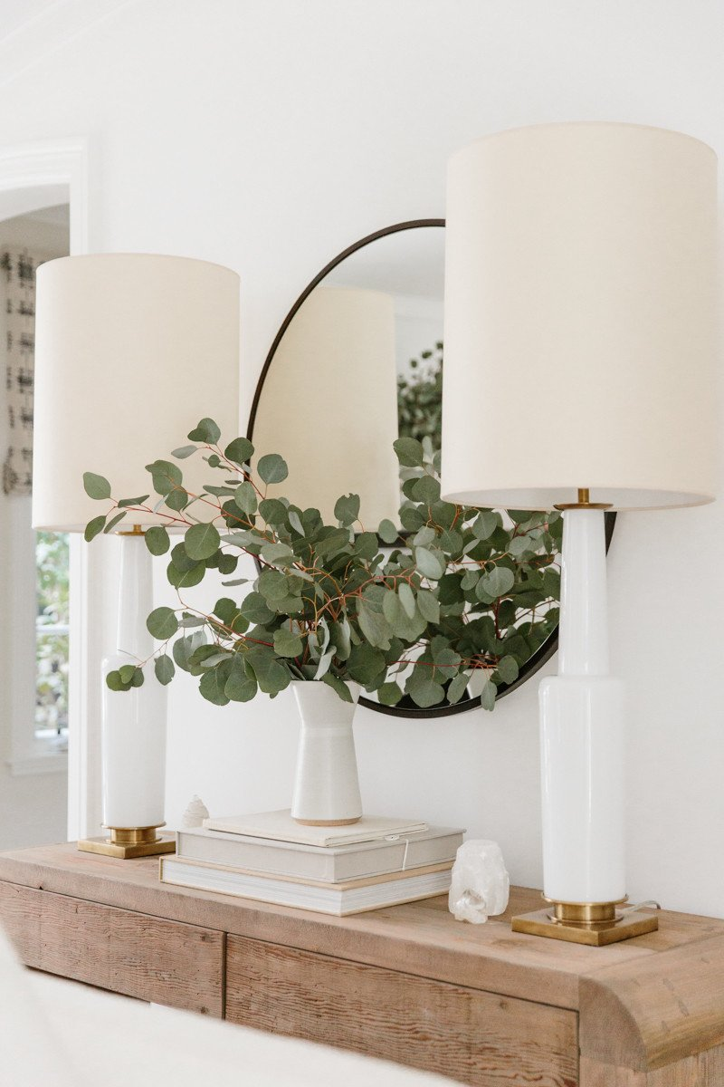 Erin Fetherston living room with rustic console table with vase of eucalyptus and white lamps