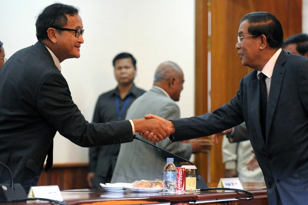 After the 2013 election, Prime Minister Hun Sen (R) shakes hands with leader of the opposition Cambodia National Rescue Party Sam Rainsy (L) during a meeting at the National Assembly, Sept. 17, 2013. AFP