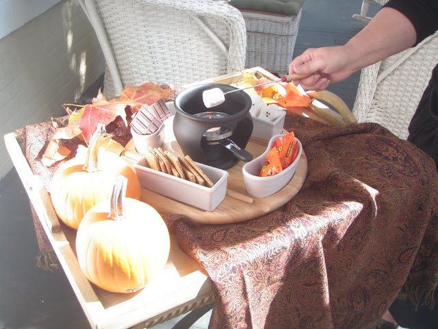 a table set with two small orange pumpkins and a smore maker with graham crackers, marshmallows roasting and chocolate bars and colorful leaves laying on the table