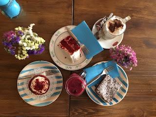 mesa com flores, bolo vermelho, cupcake e café