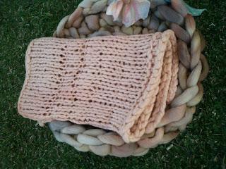 conjunto de manta e ninho com flor enfeitando, todos de lã de ovelha