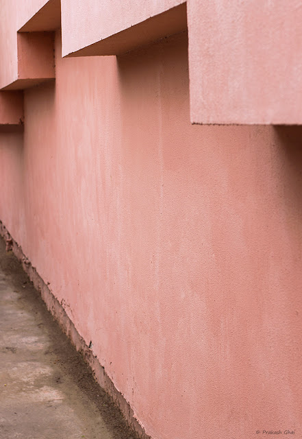 A Minimalist Photo of architectural line formation tapering towards the end on a textured pink Indian Wall Near Govind Devji Temple Jaipur.