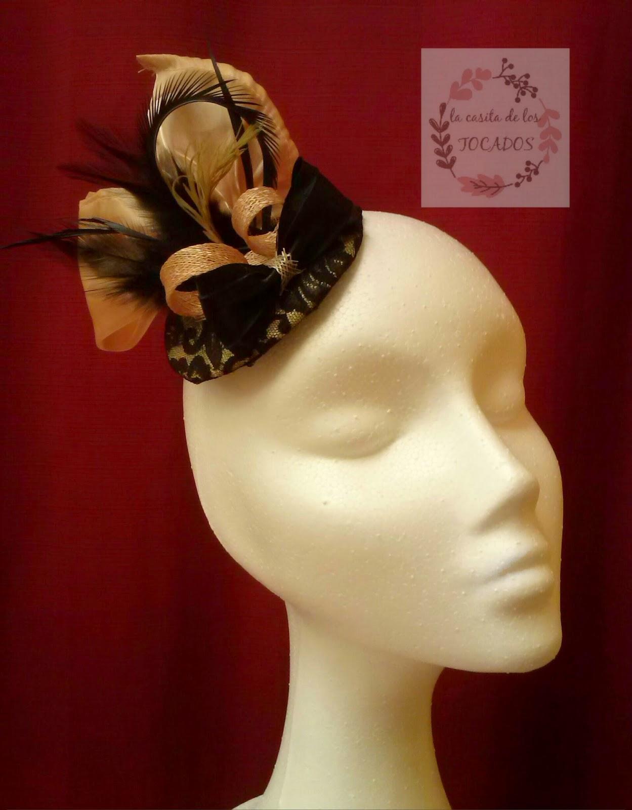 tocado con base forrada de encaje en color negro sobre fondo dorado, con adorno de organza y plumas variadas