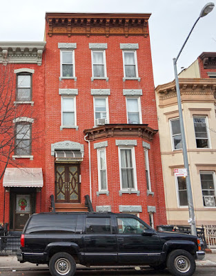 One, three story red brick row house