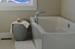 White simple bathtub with towel on basket beside it