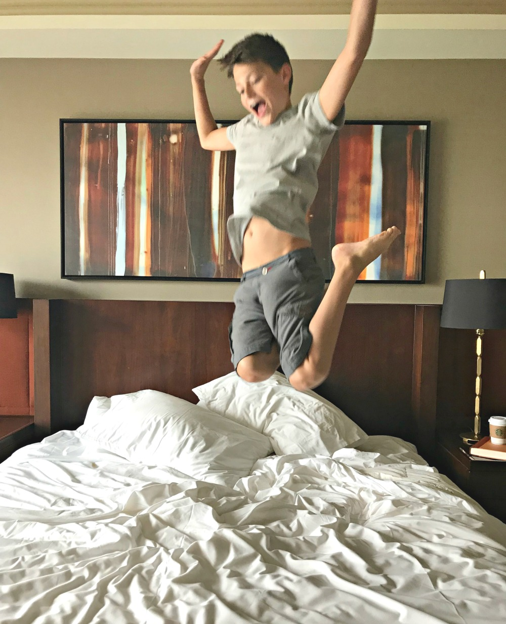 boy jumping on bed at Hyatt Regency hotel