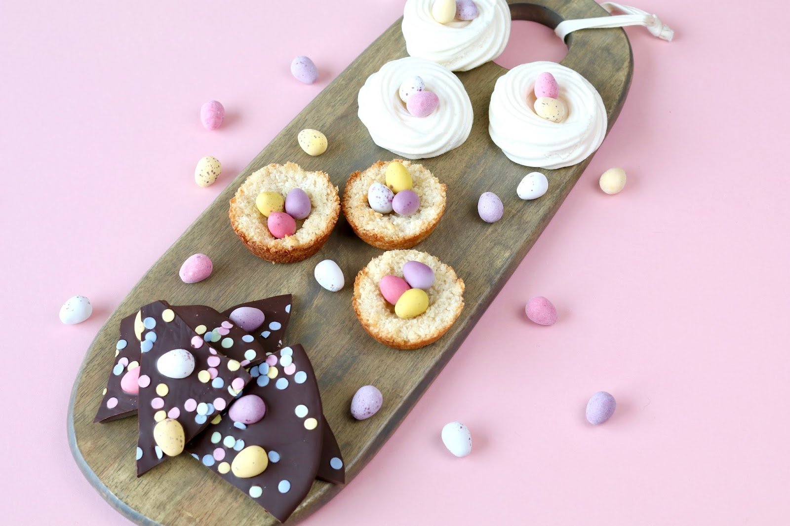 Easter treats coconut macaroons meringue nests chocolate bark with mini eggs flatlay