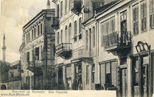 """Улицата """"Хамиди"""" околу 1907 година. Во куќата во средината на оваа слика беше сместена Печатницата """"Браќа Пили"""" во 1893 година. Разгледница од серијата, со наслов """"Souvenir de Monastir"""", во црно-бела техника, издадена околу 1907 година од браќата Пили. Бидејќи сé уште главната улица на разгледницата го носи името на султанот Хамид, годината би била 1907 а можеби и порано. Во 1908 година Широк Сокак по Младотурската револуција го промени името во улица 10 Јули или Авенија на слободата како подоцна ја преименуваа."""