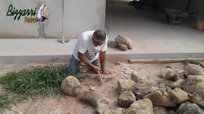 Bizzarri trabalhando, fazendo o corte das pedras moledo para fazer o revestimento de pedra na parede, com pedra moledo na cor bege com espessura de 15 a 20 cm.