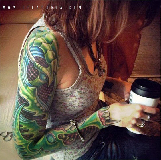 Chica con tatuaje de estilo biomecanico verde