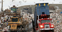 In this Wednesday, Dec. 14, 2011 file photo a garbage truck, right, empties its load as bulldozers process the waste at the Central Landfill, in Johnston, R.I. (Credit: AP Photo/Steven Senne) Click to Enlarge.