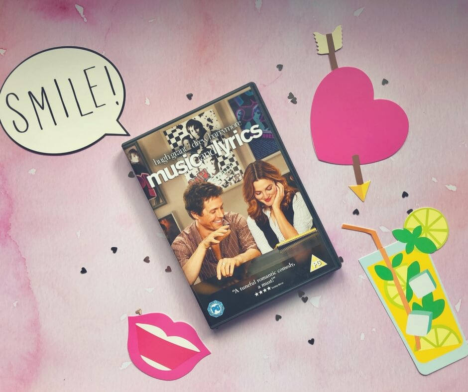 "Music and Lyrics DVD sits on a pink background surrounded by small silver hearts. In the top right corner is a pink heart with an arrow through it. In the bottom right corner is a picture of a glass of lemonade. In the bottom left corner is a smiling mouth with pink lips. In the top left corner is a speech bubble with ""Smile!"" in it."