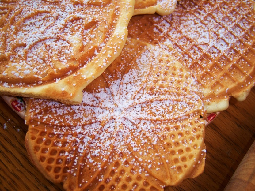 this is a cookie made on an Italian Waffle Cookie that is cooked to a golden brown color sprinkled with powdered sugar lemon, anise or vanilla flavored in the photo