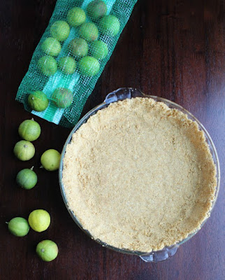 graham cracker crust in pie plate and key limes spilling out of bag