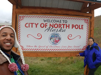 "mom and I standing in front of ""welcome to north pole"" sign"