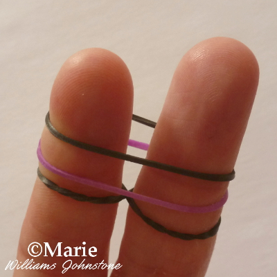 three rubber bands over the fingers black and purple