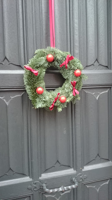 Christmas Wreath hanging on the door with red ribbon