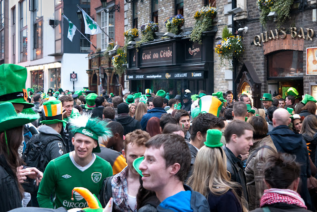 A picture of people mostly dressed in Green or Irish colours enjoying the St Patricks day celebrations outside the Quays Bar in Temple Bar