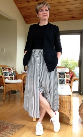 black and white striped A.L.C. midi skirt, with long sleeved black tee, black Helmut Lang blazer, and Stan Smith Adidas
