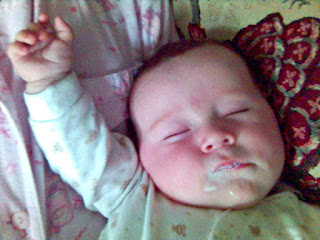 Baby fast asleep, with milk stains around face.