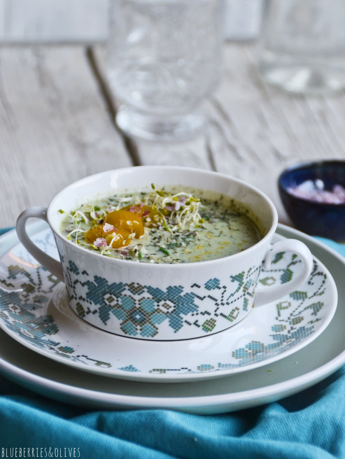 cold raw soup in vintage colorful porcelain bowl, blue tablecloth