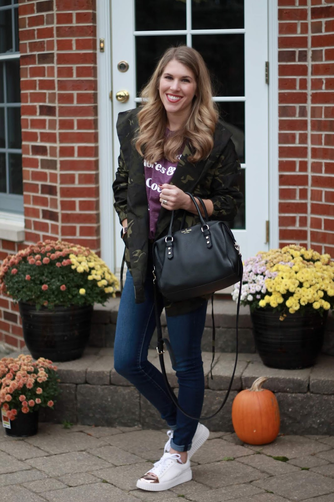 fall graphic tee, camo jacket, gold and white tennis shoes, jeans, black Kate Spade crossbody