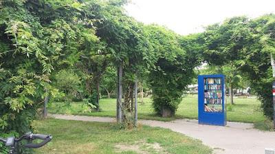 ein blauer Bücherschrank vor einem Park