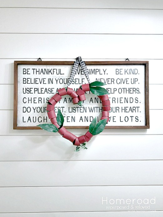 Red TP wreath hanging on a sign with shiplap wall
