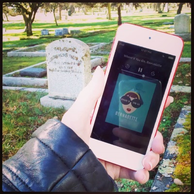 A pale hand holds a white-bordered iPod with Where'd You Go, Bernadette's turquoise cover on the screen. Behind it is a grassy, tree-shaded cemetery with a headstone close by and concrete borders around additional graves in the distance. The cover features an illustration of a dark-haired white woman wearing enormous black glasses with Where'd You Go written on them in white.