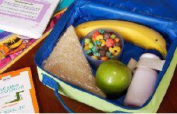 Merienda para los niños en el colegio. Lonchera con un sándwich, una banana, una manzana verde, un pote con cereales frutales y una botella pequeña. Junto al recipiente, se observa parte de dos cuadernos escolares apoyados sobre una mesa