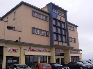 Yellow, roughcast stone finish multi-story arcade building - bingo - casino - amusements, with cars parked outside