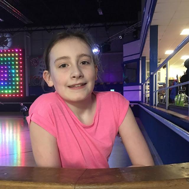 sasha smiling at side of roller rink