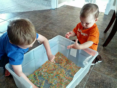 J & K exploring the colored rice and invisible letters sensory bin from And Next Comes L